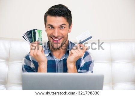 Portrait of a cheerful man holding credit cards at home - stock photo