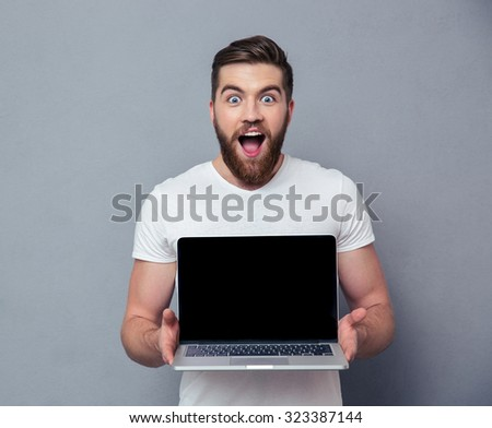 Portrait of a cheerful man showing blank laptop computer screen over gray background - stock photo