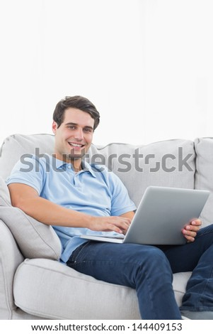 Portrait of a cheerful man using his laptop sat on a couch