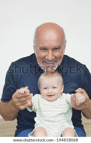 Portrait of a cheerful mature grandfather playing with grandson - stock photo