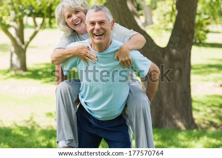 Portrait of a cheerful mature man carrying woman at the park - stock photo