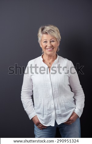 Portrait of a Cheerful Matured Woman in Casual White Shirt and Jeans, Standing Against Gray Wall Background and Smiling at the Camera. - stock photo