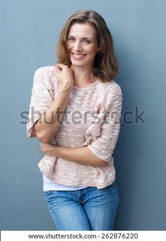 Portrait of a cheerful mid adult woman smiling in jeans and sweater - stock photo