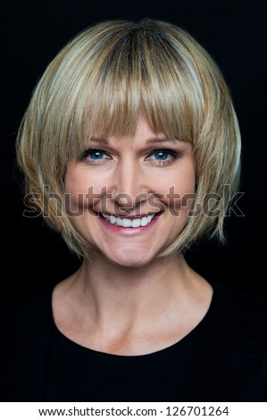Portrait of a cheerful middle aged blonde woman isolated over black background. - stock photo