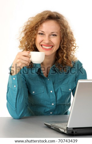 Portrait of a cheerful middle aged brunette holding coffee cup with a laptop in front