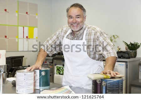 Portrait of a cheerful middle-aged sales clerk with paint can in hardware store - stock photo