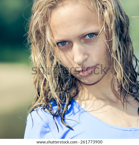 Portrait of a cheerful pleasant blonde girl with blue eyes and wet hair - stock photo