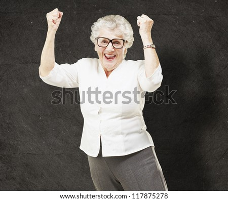 portrait of a cheerful senior woman gesturing victory against a grunge wall - stock photo