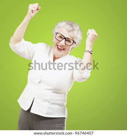 portrait of a cheerful senior woman gesturing victory over green background