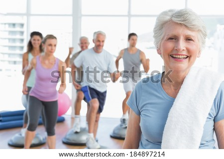 Portrait of a cheerful senior woman with people exercising in the background at fitness studio - stock photo