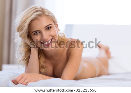 Portrait of a cheerful sexy woman lying on the bed at home - stock photo