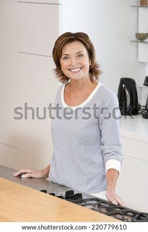 Portrait of a cheerful, smiling mature woman standing at oven in kitchen looking to camera - stock photo
