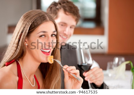 Portrait of a cheerful woman eating food with man having drink - stock photo