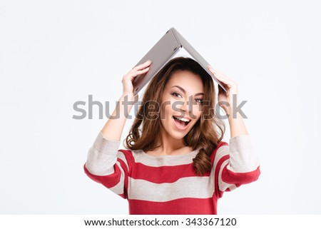 Portrait of a cheerful woman holding laptop computer over head isolated on a white background - stock photo
