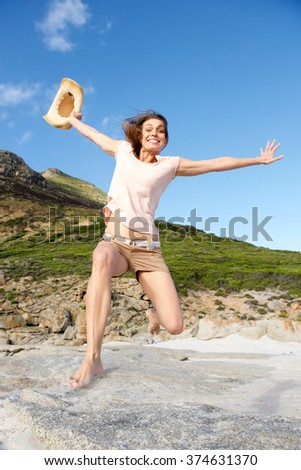 Portrait of a cheerful woman jumping outdoors - stock photo