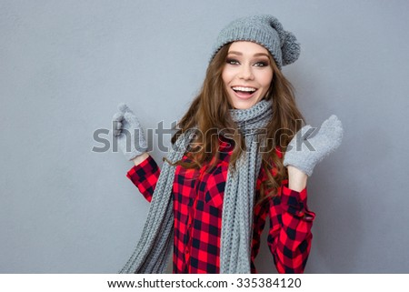 Portrait of a cheerful woman looking at camera over gray background - stock photo