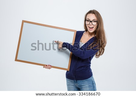 Portrait of a cheerful woman pointing finger on blank board isolated on a white background - stock photo
