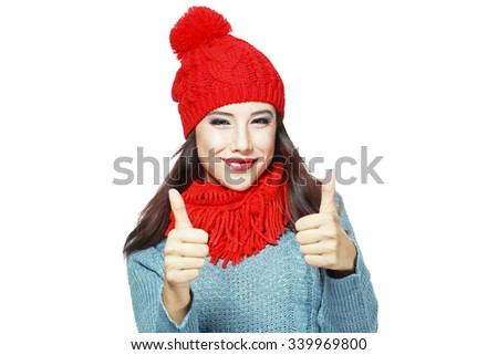 Portrait of a cheerful woman showing thumbs up over gray background - stock photo