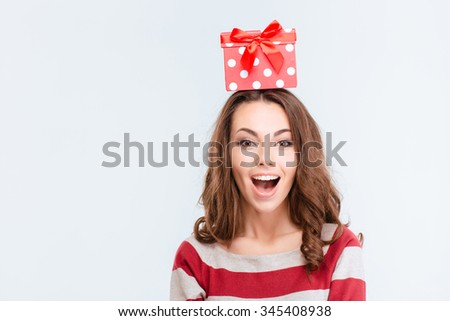 Portrait of a cheerful woman with gift box on head standing isolated on a white background - stock photo