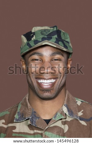 Portrait of a cheerful young African American US Marine Corps soldier over brown background - stock photo