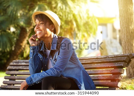 Portrait of a cheerful young african american woman sitting outside - stock photo