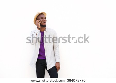 Portrait of a cheerful young african guy talking on cell phone against white background - stock photo
