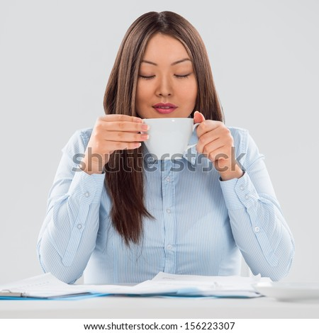 Portrait of a cheerful young business woman holding coffee cup with papers in front