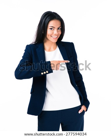 Portrait of a cheerful young businesswoman pointing finger away. Standing over white background. Looking at camera - stock photo