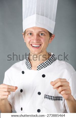 Portrait of a cheerful young cook. Vertical photo - stock photo