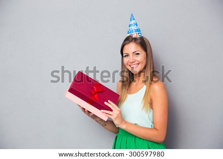 Portrait of a cheerful young girl celebrating her birthday over gray background - stock photo