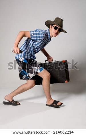 Portrait of a cheerful young guy tourist. A man with a suitcase going dark glasses and a hat - stock photo