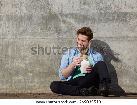 Portrait of a cheerful young man eating chinese take away food with chopsticks - stock photo
