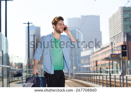 Portrait of a cheerful young man standing at train station platform with mobile phone - stock photo