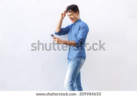 Portrait of a cheerful young man walking and reading text message on cell phone - stock photo