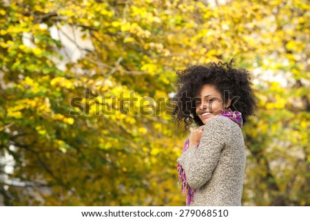 Portrait of a cheerful young mixed race woman smiling outdoors - stock photo