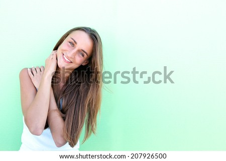 Portrait of a cheerful young woman posing against green background