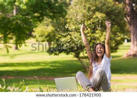 Portrait of a cheerful young woman raising hands with laptop in the park - stock photo