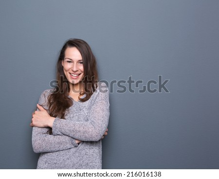 Portrait of a cheerful young woman smiling with arms crossed on gray background - stock photo