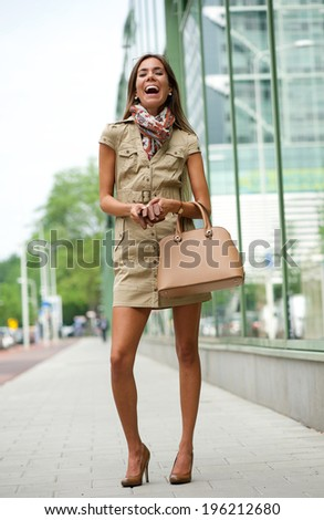 Portrait of a cheerful young woman standing on sidewalk in the city with handbag - stock photo