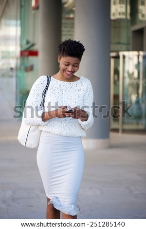 Portrait of a cheerful young woman walking on sidewalk and sending text message on mobile phone - stock photo
