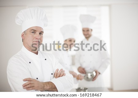 portrait of a chef and his kitchen team