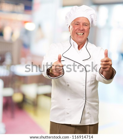 Portrait Of A Chef Cook With Hand Sign, Indoor - stock photo