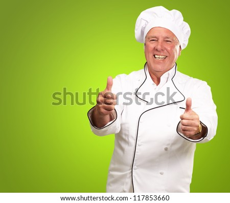 Portrait Of A Chef Cook With Hand Sign On Green Background - stock photo