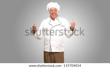 Portrait Of A Chef Cook With Hand Sign On Grey Background - stock photo