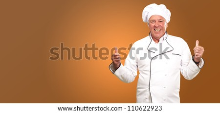 Portrait Of A Chef Cook With Hand Sign On Yellow Background