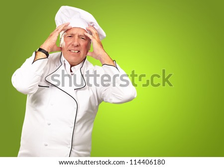 Portrait Of A Chef Having Headache Isolated On Green Background - stock photo