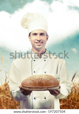 Portrait of a chef holding a loaf of bread against a wheat field background - stock photo
