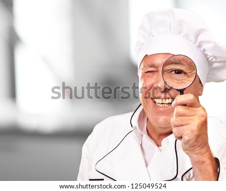 Portrait Of A Chef Holding Magnifying Glass, Indoor - stock photo