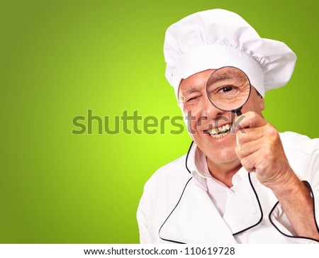 Portrait Of A Chef Holding Magnifying Glass Isolated On Green Background - stock photo