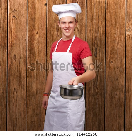 Portrait Of A Chef Holding Pan, Indoor - stock photo